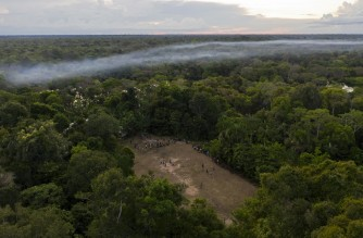 Aerial view of a football game taking place in a forest clearing in the Bauana community, municipality of Carauari, in the heart of the Brazilian Amazon Forest, on March 15, 2020. - Many young people in the heart of the Amazon rainforest choose their community over the city. (Photo by Florence GOISNARD / AFP)