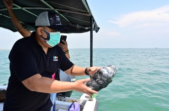 This picture taken on October 20, 2020 shows Eric Ragaputra, a technician from the CLS Argos company, about to throw a plastic monitoring device with satellite beacons into the sea to monitor waste off the coast of Teluk Naga, Tangerang, Banten province. - Scientists are turning to satellite technology to trace this mountain of waste and figure out how the world's second-biggest marine waste contributor -- second only to China -- can tackle the mess. (Photo by ADEK BERRY / AFP) / TO GO WITH STORY: Indonesia environment oceans satellite, FOCUS by Lucie GODEAU