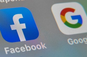 (FILES) In this file photo illustration taken on October 01, 2019, shows the logos of mobile apps  Facebook and Google displayed on a tablet in Lille France. - Facebook and Google have extended their bans on political ads in the US amid misinformation circulated aimed at bolstering claims by President Donald Trump of fraud in his loss to Joe Biden. (Photo by DENIS CHARLET / AFP)