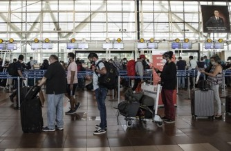 People queue at the counters at Arturo Merino Benitez International Airport in Santiago, on November 23, 2020, after Chile resumed international flights after eight months of tight restrictions amid the spread of the novel coronavirus disease, COVID-19 (Photo by Martin BERNETTI / AFP)