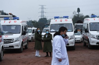 Rescue personnel wait beside parked ambulances outside the Diaoshuidong coal mine in southwestern China's Chongqing on December 5, 2020, after a carbon monoxide leak at the facility left 18 dead, with rescue efforts under way to reach five others still trapped underground. (Photo by STR / AFP) / China OUT