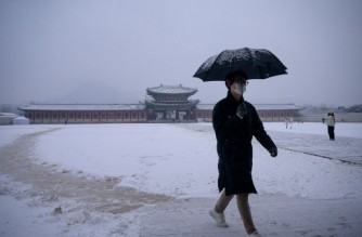 A visitor walks through a courtyard covered in snow at Gyeongbokgung palace in central Seoul on December 13, 2020. (Photo by Ed JONES / AFP)