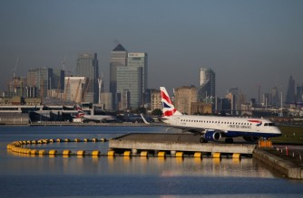 (FILES) This file photo taken on October 27, 2017 shows a British Airways airplane waiting on the runway with the towers and buildings of London's Canary Wharf financial district in background before taking off at London City Airport in London. - Germany is considering banning flights from Britain and South Africa to prevent the spread of new, more infectious coronavirus strain circulating in the two countries, a source close to the German health ministry told AFP on Sunday, December 20, 2020. (Photo by Daniel LEAL-OLIVAS / AFP)