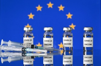 (FILES) This illustration photo taken on November 17, 2020 shows vials with Covid-19 Vaccine stickers attached, and syringes, with a flag of the European Union. The EU's drug regulator authorised the Pfizer-BioNTech coronavirus vaccine on December 21, 2020, and said there was no evidence it would not work against a new strain found mainly in Britain. (Photo by JUSTIN TALLIS / AFP)