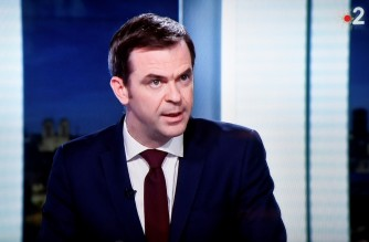 French Health and Solidarity Minister Olivier Veran is seen on a television screen as he takes part in the evening news broadcast of French public TV channel France 2 on December 29, 2020, in Paris, amid the Covid-19 pandemic, caused by the novel coronavirus. (Photo by STEPHANE DE SAKUTIN / AFP)