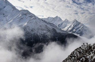 Agence France-Presse reporter Ammu Kannampilly (2R), and Nepalese guide Pasang Sherpa (R) stand on a ridge over a valley leading north into the Khumbu region as they try to get a clear view of Mt. Everest on April 18, 2015.   AFP PHOTO/ROBERTO SCHMIDT (Photo by Roberto SCHMIDT and - / AFP)