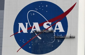 CAPE CANAVERAL, FLORIDA - MAY 28: Workers repaint the NASA logo on the Vehicle Assembly Building at the Kennedy Space Center on May 28, 2020 in Cape Canaveral, Florida. SpaceXs Crew Dragon spacecraft will try to launch again on Saturday after weather scrubbed yesterday's attempt. It will be the first manned mission since the end of the Space Shuttle program in 2011 to be launched into space from the United States.   Joe Raedle/Getty Images/AFP