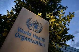 A photo taken in the late hours of August 17, 2020 shows a sign of the World Health Organization (WHO) at their headquarters in Geneva amid the COVID-19 outbreak, caused by the novel coronavirus. (Photo by Fabrice COFFRINI / AFP)