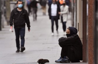 A man begs for money along a street in Melbourne's city centre on September 17, 2020. - Australia's unemployment rate on September 17 fell slightly to 6.8 percent in August, spurring hopes that the worst of a coronavirus-fuelled recession may have passed. (Photo by William WEST / AFP)