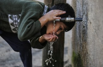 A Palestinian boy drinks water from a tap in the town of Khan Yunis in southern Gaza Strip, on November 18, 2020. - The densely-populated Gaza Strip has long lacked sufficient drinking water, but a new project helps ease the shortage with a solar-powered process to extract potable water straight from the air. (Photo by SAID KHATIB / AFP)