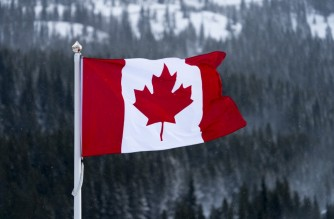 "(FILES) In this file photo the Canadian flag flies over the Lake Louise ski lodge in the Canadian Rockies November 29, 2017 in Lake Louise, Alberta. - Canada will halt the entry of passenger flights from Britain for 72 hours from midnight Sunday December 20, authorities announced, the latest nation to take action over a new fast-spreading strain of coronavirus in the UK. ""Given the high number of cases of a variant Covid-19 virus observed in some areas in the United Kingdom, the decision has been made to suspend entry into Canada of all commercial and private passenger flights from the United Kingdom for 72 hours,"" said a statement from Canadian health authorities. (Photo by Don EMMERT / AFP)"