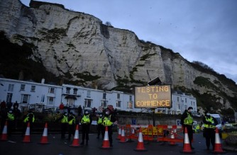 "Police officers stand on duty at beneath a sign reading ""Testing to Commence"", at the entrance to the Port of Dover in Kent, south east England, on December 23, 2020, where COVID-19 testing is set to begin on drivers who have been queueing to leave the UK. - France and Britain reopened cross-Channel travel on Wednesday after a 48-hour ban to curb the spread of a new coronavirus variant but London has warned it could take days for thousands of trucks blocked around the port of Dover to get moving. (Photo by JUSTIN TALLIS / AFP)"