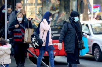 Iranians wearing protective masks amid the COVID-19 pandemic, leave a bus in the capital Tehran, on December 30, 2020. (Photo by ATTA KENARE / AFP)