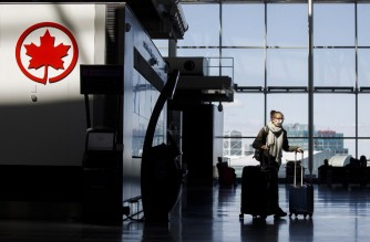 (FILES) In this file photo taken on April 1, 2020, a passenger wheels her luggage near an Air Canada logo at Toronto Pearson International Airport in Toronto, Canada. - Canada will require travellers to obtain a negative Covid-19 test before being allowed into the country, the government announced on December 30, 2020. (Photo by Cole Burston / GETTY IMAGES NORTH AMERICA / AFP)