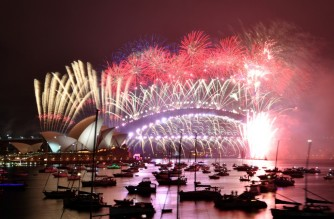 """This handout picture released by NSW Government through AAP Images shows the New Year's Eve fireworks erupting over Sydney's iconic Harbour Bridge and Opera House (L) during the fireworks show on January 1, 2021. (Photo by MICK TSIKAS / AAP IMAGES FOR NSW GOVERNMENT / AFP) / ---EDITORS NOTE ----RESTRICTED TO EDITORIAL USE MANDATORY CREDIT """" AFP PHOTO /AAP IMAGES FOR NSW GOVERNMENT/ Mick Tsikas/ NO MARKETING NO ADVERTISING CAMPAIGNS - DISTRIBUTED AS A SERVICE TO CLIENTS-"""