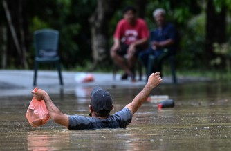 A man carries foods through floodwaters in Lanchang in Malaysia's Pahang state on January 4, 2021. (Photo by Mohd RASFAN / AFP)