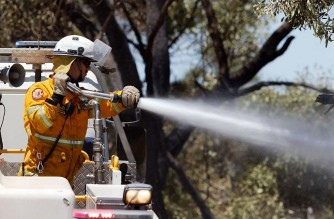 A firefighter sprays a hose from his truck to put out spot fires while battling a bush fire in Kwinana, some 30 kilometres south of Perth on January 4, 2021. (Photo by TREVOR COLLENS / AFP)