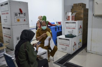 Indonesian health staff check Sinovac vaccines for the Covid-19 coronavirus at a storage facility before they are distributed to other provinces, in Banda Aceh on January 5, 2021. (Photo by CHAIDEER MAHYUDDIN / AFP)