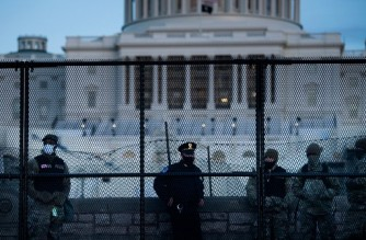 A Capitol Police officer stands with members of the National Guard behind a crowd control fence surrounding Capitol Hill a day after a pro-Trump mob broke into the US Capitol on January 7, 2021, in Washington, DC. (Photo by Brendan Smialowski / AFP)
