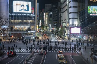 Pedestrians walk at crossing of Shibuya district in Tokyo on January 8, 2021, during the first day under a state of emergency over the Covid-19 coronavirus pandemic. (Photo by Philip FONG / AFP)