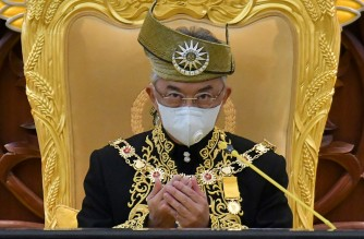 """(FILES) This handout photo from Malaysia's Department of Information taken and released on May 18, 2020 shows Malaysia's King Sultan Abdullah Sultan Ahmad Shah wearing a face mask as he offers prayers during the opening ceremony for the third term of the 14th parliamentary session in Kuala Lumpur. - Malaysia's King Sultan Abdullah Sultan Ahmad Shah on January 12, 2021 declared a nationwide state of emergency to fight a surge in COVID-19 coronavirus cases that threatens to overwhelm the country's healthcare system. (Photo by NAZRI RAPAAI / Malaysia's Department of Information / AFP) / -----EDITORS NOTE --- RESTRICTED TO EDITORIAL USE - MANDATORY CREDIT """"AFP PHOTO / MALAYSIA'S DEPARTMENT OF INFORMATION/  NAZRI RAPAAI """" - NO MARKETING - NO ADVERTISING CAMPAIGNS - DISTRIBUTED AS A SERVICE TO CLIENTS"""