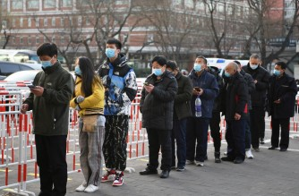 Residents line up outside a community centre to be vaccinated against the COVID-19 coronavirus in Beijing on January 12, 2021. (Photo by GREG BAKER / AFP)