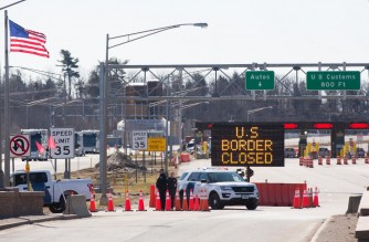 "(FILES) In this file photo taken on March 22, 2020 US Customs officers stand beside a sign saying that the US border is closed at the US/Canada border in Lansdowne, Ontario. - The Canada-US border will remain closed to all non-essential travelers until February 21, Prime Minister Justin Trudeau announced January 12, 2021. ""This morning I can confirm that Canada will extend by another 30 days, until February 21, the border measures that are currently in place with the United States,"" Trudeau told a news conference. (Photo by Lars Hagberg / AFP)"