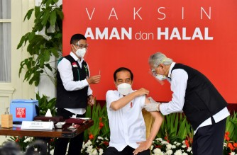 "This handout photo taken and released on January 13, 2021 by Indonesia's Presidential Palace shows Indonesian President Joko Widodo (C) receiving the country's first Covid-19 vaccine jab at the Presidential Palace in Jakarta, kicking off a mass innoculation drive in a bid to control soaring case rates. (Photo by HANDOUT / Indonesia's Presidential Palace / AFP) / RESTRICTED TO EDITORIAL USE - MANDATORY CREDIT ""AFP PHOTO / INDONESIA'S PRESIDENTIAL PALACE "" - NO MARKETING - NO ADVERTISING CAMPAIGNS - DISTRIBUTED AS A SERVICE TO CLIENTS"