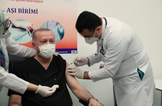 """This handout picture taken on January 14, 2021 and released by Turkish Presidential Press Service shows Turkish President Recep Tayyip Erdogan (C) receiving the first dose of the CoronaVac Covid-19 vaccine at Ankara City Hospital in Ankara. (Photo by - / TURKISH PRESIDENTIAL PRESS SERVICE / AFP) / RESTRICTED TO EDITORIAL USE - MANDATORY CREDIT """"AFP PHOTO / Turkish Presidential Press Service """" - NO MARKETING - NO ADVERTISING CAMPAIGNS - DISTRIBUTED AS A SERVICE TO CLIENTS"""