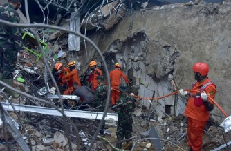 Rescuers search for survivors at a collapsed building in Mamuju on January 15, 2021, after a 6.2-magnitude earthquake rocked Indonesia's Sulawesi Island. (Photo by Firdaus / AFP)
