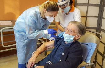 """A photo taken and handout on January 18, 2021 by the communications office of the Italian healthcare Kos Group, shows the vaccination against COVID-19 of 108-years-old Fatima Negrini (R), a resident at the group's Anni Azzurri San Faustino residence in Milan who tested positive to the coronavirus in May 2020. - An Italian centenarian who survived a coronavirus infection in May has become one of the oldest people in the world to get a Covid-19 vaccine, her retired home said. Fatima Negrini, who is due to turn 109 on June 3, received the jab on january 18, 2021 along with other residents of the Anni Azzurri San Faustino care home in Milan. (Photo by Handout / KOS GROUP / AFP) / RESTRICTED TO EDITORIAL USE - MANDATORY CREDIT """"AFP PHOTO / KOS GROUP / HANDOUT"""" - NO MARKETING - NO ADVERTISING CAMPAIGNS - DISTRIBUTED AS A SERVICE TO CLIENTS"""