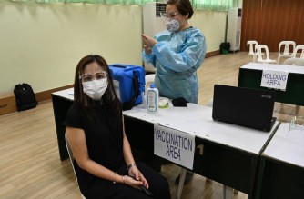 A city hall employee (L) takes part in a vaccination simulation in Manila on January 19, 2021, ahead of the expected arrival of COVID-19 coronavirus vaccines in the capital city next month. (Photo by Ted ALJIBE / AFP)