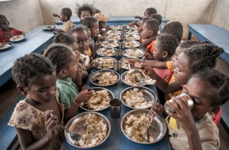 (FILES) In this file photograph taken on December 14, 2018, schoolchildren from Ankileisoke Primary School eat lunch, offered by the World Food Programme's Under-nutrition Prevention Programme, in the Amboasary-South district of southern Madagascar. In addition to ensuring that children can eat at least once a day, this program also ensures that children come to school. - The United Nations said January 19, 2021, that USD76 million was urgently needed to help over one million people in southern Madagascar facing potentially life-threating shortages of food, water and health assistance. The UN humanitarian agency OCHA issued its so-called flash appeal after the impoverished island country in eastern Africa saw its agricultural season ruined by the worst drought in a decade. At the same time, the economic impact of the Covid-19 pandemic and the lockdowns implemented to halt the spread of the virus have amplified the hit from the drought -- the third in a row, it said. (Photo by RIJASOLO / AFP)