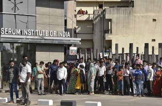 People stand outside the India's Serum Institute after a fire broke out, in Pune on January 21, 2021. - A fire broke out on January 21 at India's Serum Institute, the world's largest maker of vaccines, but a company source said production of drugs to prevent Covid-19 coronavirus was not affected. (Photo by - / AFP)