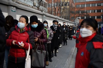 People line up to be tested for the Covid-19 coronavirus in Beijing on January 22, 2021, part of a drive to test two million people in 48 hours as the city rushes to snuff out a new local cluster of cases believed to be linked to a more contagious virus variant. (Photo by GREG BAKER / AFP)