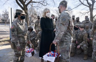 """Saying, """"The Biden's are a National Guard family,"""" first lady Jill Biden greets members of the National Guard with chocolate chip cookies outside the Capitol on January 22, 2021, in Washington, DC. (Photo by Jacquelyn Martin / POOL / AFP)"""
