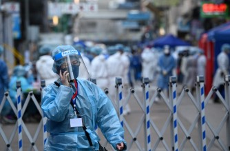 A health worker uses her phone as authorities conduct testing in the Jordan area of Hong Kong on January 23, 2021, after thousands were ordered to stay in their homes for the city's first COVID-19 coronavirus lockdown as authorities battle an outbreak in one of its poorest and most densely packed districts. (Photo by Peter PARKS / AFP)