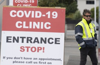 (FILES) This file photo taken on April 20, 2020 shows a security guard standing outside a COVID-19 coronavirus clinic in Lower Hutt, near Wellington. - New Zealand health officials on January 24, 2021 confirmed the first case of Covid-19 in the community for more than two months, sparking urgent contract-tracing efforts north of Auckland. (Photo by Marty MELVILLE / AFP)