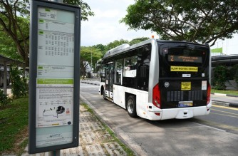 An on-demand autonomous bus developed by ST Engineering departs from bus stop after picking up passengers at the start of a trial run from Singapore Science Park 2 to Haw Par Villa MRT station in Singapore on January 26, 2021. (Photo by Roslan RAHMAN / AFP)
