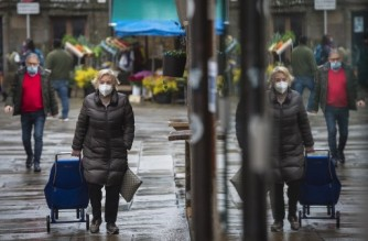 A woman wearing a face mask pulls a trolley as she goes to the food market in Santiago de Compostela, northwestern Spain, on January 27, 2021. - Spain has recorded more than 55,000 deaths from nearly 2.5 million cases of Covid-19 so far. (Photo by MIGUEL RIOPA / AFP)