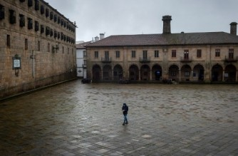 A person walks along the empty Quintana Square, next to the Cathedral, in downtown Santiago de Compostela, northwestern Spain, on January 27, 2021. - Spain has recorded more than 55,000 deaths from nearly 2.5 million cases of Covid-19 so far. (Photo by MIGUEL RIOPA / AFP)