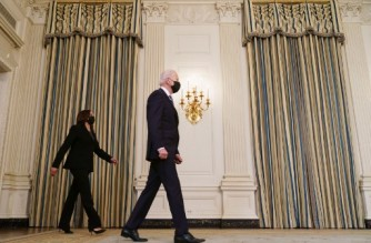 US President Joe Biden (R) and Vice President Kamala Harris arrive in the State Dining Room for Biden's address on climate change before signing executive orders in the State Dining Room of the White House in Washington, DC on January 27, 2021. (Photo by MANDEL NGAN / AFP)