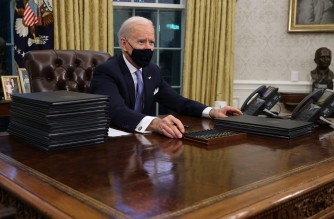 WASHINGTON, DC - JANUARY 20: U.S. President Joe Biden prepares to sign a series of executive orders at the Resolute Desk in the Oval Office just hours after his inauguration on January 20, 2021 in Washington, DC. Biden became the 46th president of the United States earlier today during the ceremony at the U.S. Capitol.   Chip Somodevilla/Getty Images/AFP