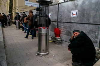 """Homeless people practice social distancing as they queue up for a meal at the """"Rescue Hangar"""" during the COVID-19 coronavirus lockdown, in Moscow on April 27, 2020. (Photo by Dimitar DILKOFF / AFP)"""