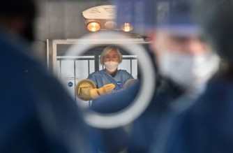 A medical staff member (C) wearing protective gear in a booth prepares to give tests for the COVID-19 coronavirus at a temporary testing station outside the City Hall in Seoul on December 23, 2020, as South Korea banned gatherings of more than four people in the capital and surrounding areas amid a surge in infection cases. (Photo by Jung Yeon-je / AFP)