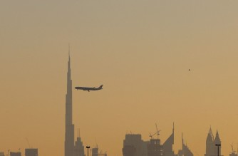 A commercial airplane flies past Burj Khalifa as it starts landing at Dubai international airport in the United Arab Emirates, on January 9, 2021. - As much of the world tightens lockdowns to stem coronavirus, Dubai has flung its doors open, branding itself as a sunny, quarantine-free escape -- despite a sharp rise in cases. (Photo by GIUSEPPE CACACE / AFP)