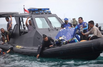 Divers bring up a piece of debris from the crash site of Sriwijaya Air flight SJ182 off the coast north of Jakarta on January 14, 2021, during search operations off the coast for the Boeing 737-500 which crashed into the Java Sea minutes after takeoff on January 9. (Photo by Demy Sanjaya / AFP)
