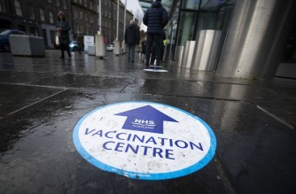 Members of the public pass an NHS Scotland vaccination centre set up at the Edinburgh International Conference Centre (EICC) in Edinburgh on February 1, 2021. - Britain is under a third national lockdown as it battles a new strain of the virus and has recorded more than 106,000 deaths from the disease -- the worst toll in Europe. (Photo by Jane Barlow / POOL / AFP)