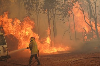 """This handout photo taken on February 2, 2021 and released by West Australia's Department of Fire and Emergency Services (DFES) shows a firefighter fighting a fire outside Wooroloo, near Australia's fourth-biggest city Perth. (Photo by Evan COLLIS / Department of Fire and Emergency Services / AFP) / -----EDITORS NOTE --- RESTRICTED TO EDITORIAL USE - MANDATORY CREDIT """"AFP PHOTO / Department of Fire and Emergency Services"""" - NO MARKETING - NO ADVERTISING CAMPAIGNS - DISTRIBUTED AS A SERVICE TO CLIENTS"""