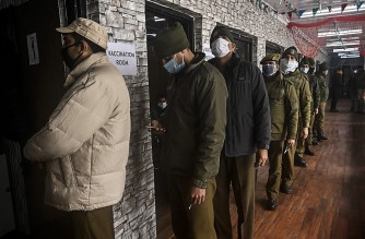 Police personnel stand in a queue for a Covid-19 coronavirus vaccine at the Police headquarters in Srinagar on February 4, 2021. (Photo by Tauseef mustafa / AFP)